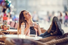 Image of a smiling young woman sitting at a cafe with her feet up while she holds a small cup of coffee