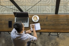 Image of young man sitting at his laptop in a coffee shop writing something down in a notebook
