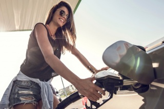 Woman filling tank at gas pump