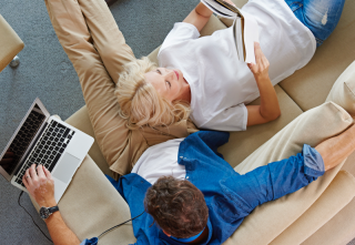 couple on couch looking at laptop and book
