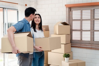 first-time home buyers moving boxes in their new home