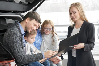 a family signs paperwork at the dealership to seal the deal on their new family car