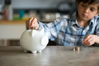 child putting coin in piggybank