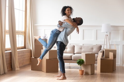 first time home buyer couple embraces in their new living room