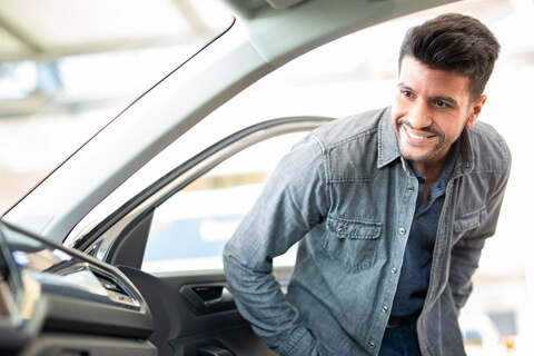 man smiling looking inside a new car he wants to purchase with a 72-month auto loan