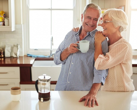 couple drinking coffee in bright kitchen