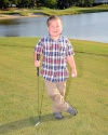 Young boy with golf club on green