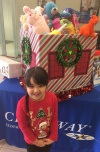 young girl in red holiday sweater stands in front of table with a box overflowing with toys